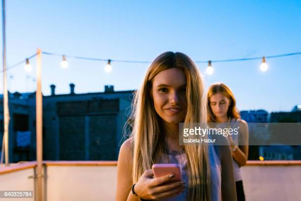 Young woman using smart phone at the rooftop party
