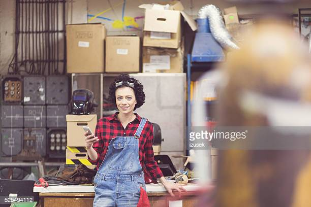 Young woman using smart phone in a workshop