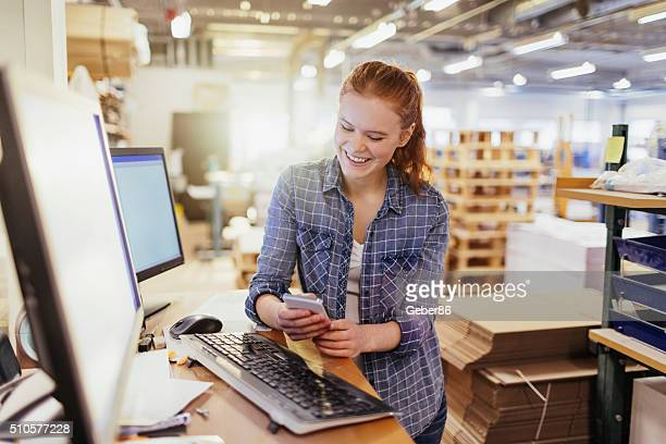 Young woman using smart phone in printing factory