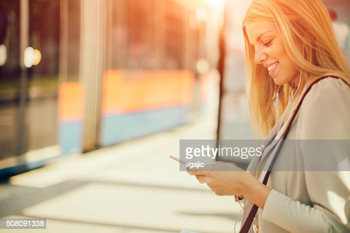 Young Woman Using Smart Phone on Bus Station