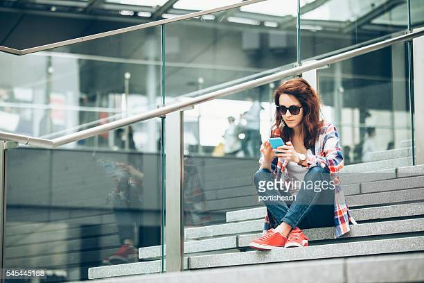 Young woman using smart phone on stairs
