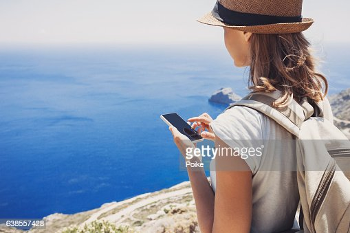Young woman using smart phone on vacations : Foto stock
