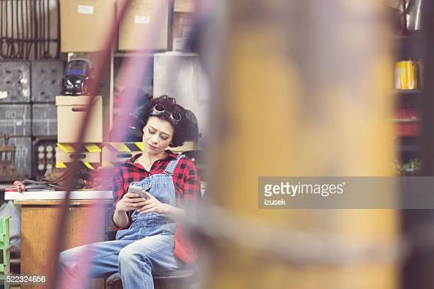 Jeune femme à l'aide de téléphone intelligent, assis dans un atelier de soudure