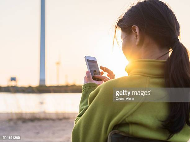 Young woman using smart phone under sunset.