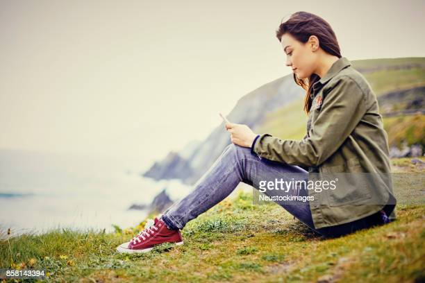 Young woman using smart phone while sitting on mountain