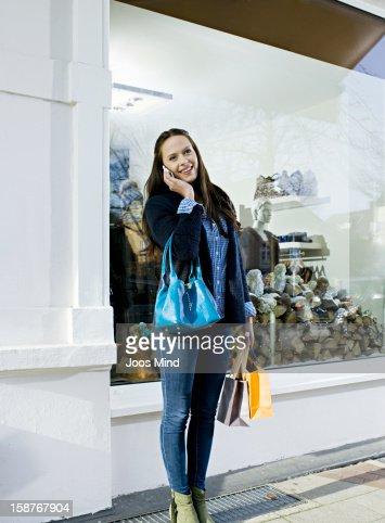 young woman using smart phone, window shopping : Stock Photo