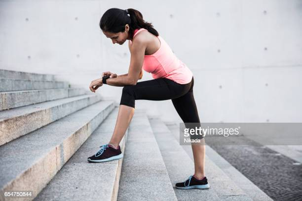 Young woman using smart watch for the running in the city.