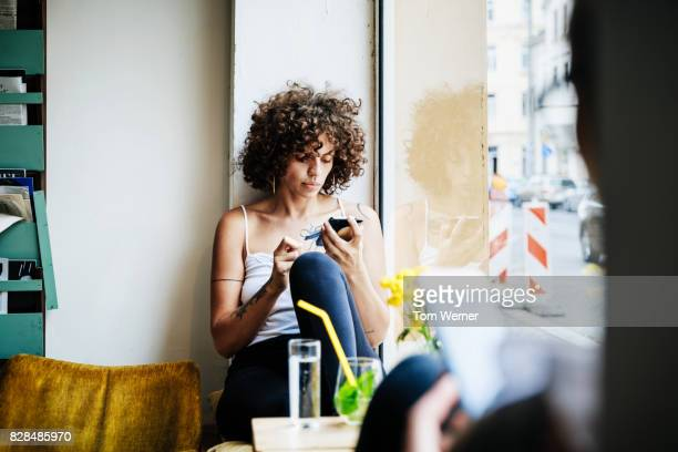 Young Woman Using Smartphone At Cafe