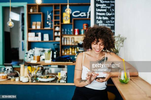 Young Woman Using Smartphone In Colourful Cafe