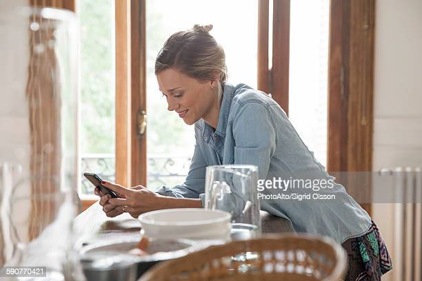 Young woman using smartphone in kitchen