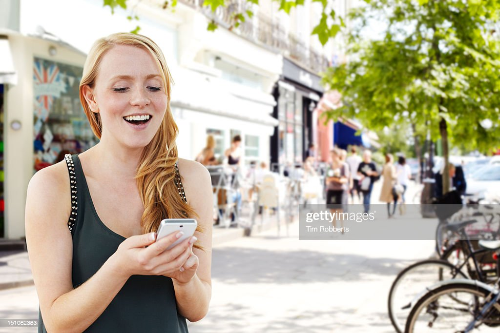Young woman using smartphone on street : Stock Photo