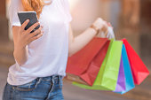 Young woman using smartphone with a shopping bag in other hand,Shopping concepts.