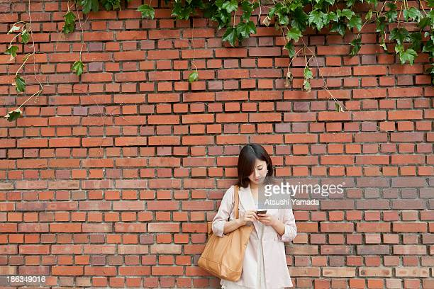 Young woman using smartphone,leaning to brick wall