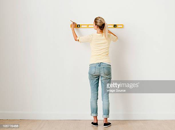 Young woman using spirit level on wall