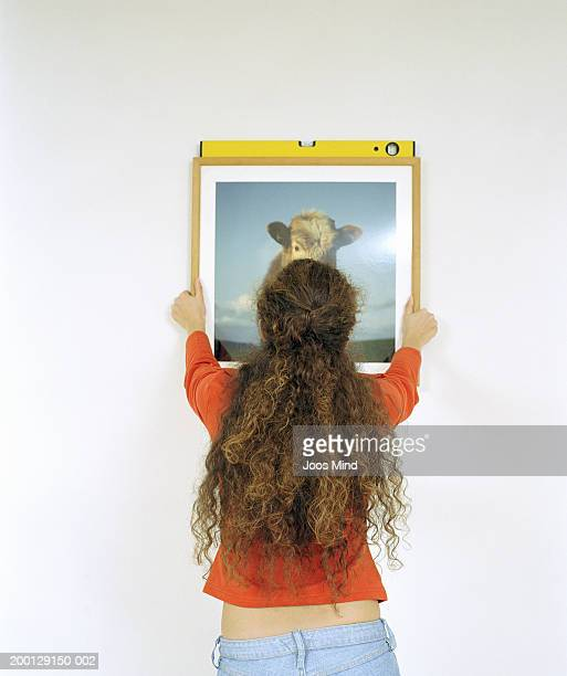 Young woman using spirit level to hang picture on wall, rear view
