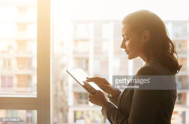 Young Woman Using Tablet Computer at Sunset