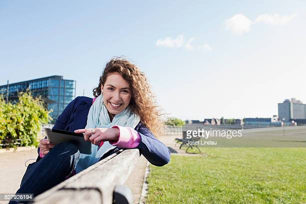 Young woman using tablet computer in park