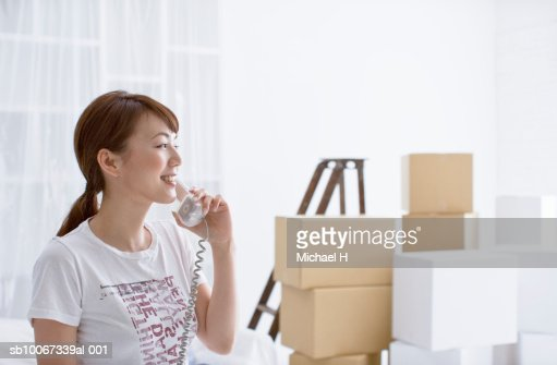 Young woman using telephone in room with cardboard boxes