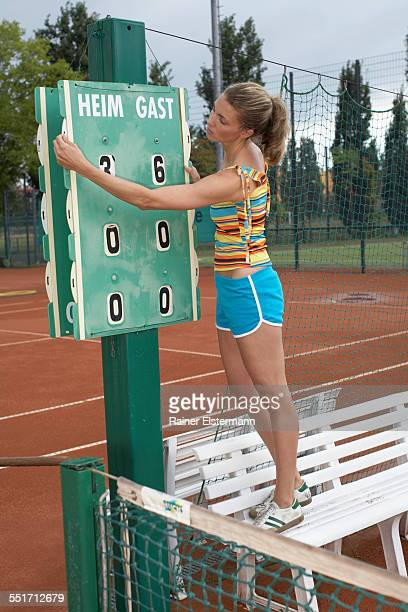 Young Woman Using Tennis Scoreboard
