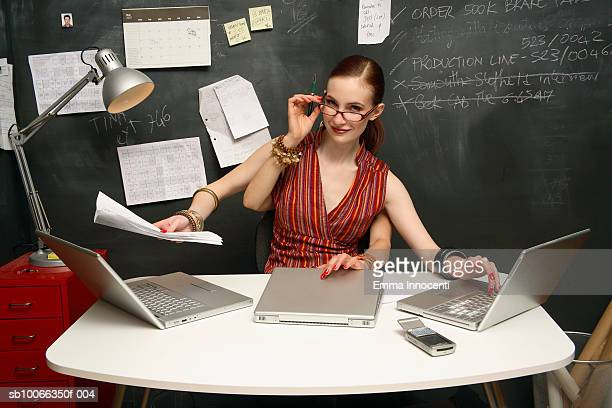 Young woman using three laptops with four hands, smiling, portrait