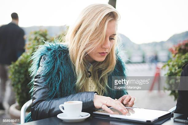 Young woman using touchscreen on digital tablet at sidewalk cafe, Lake Como, Como, Italy