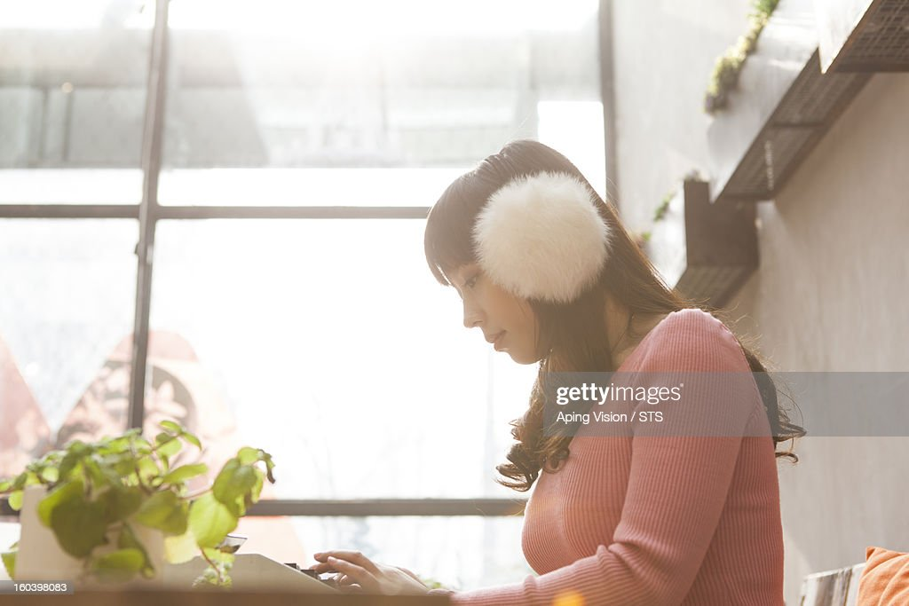 Young woman using typewriter indoor : Stock Photo