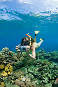 Young woman using underwater camera, snorkelling on coral reef