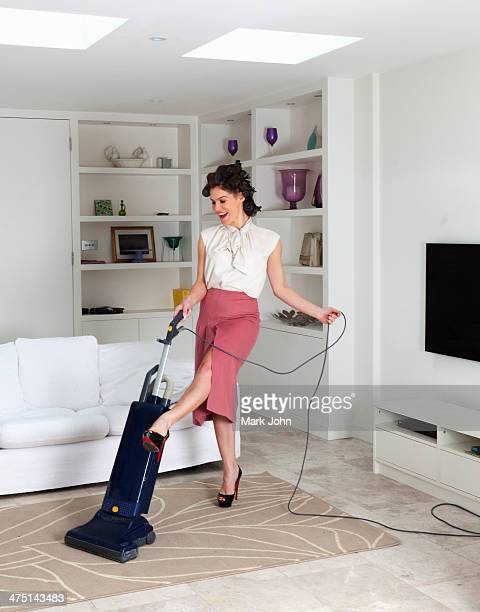Young woman using vacuum cleaner in living room