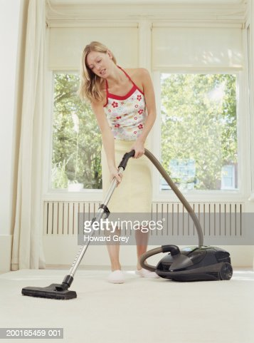 Young woman using vacuum cleaner : Foto de stock