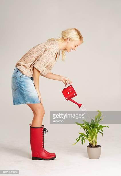 Young woman using watering can to water plant