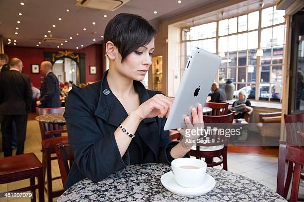 Young woman using wifi Internet on Apple iPad in coffee shop London UK