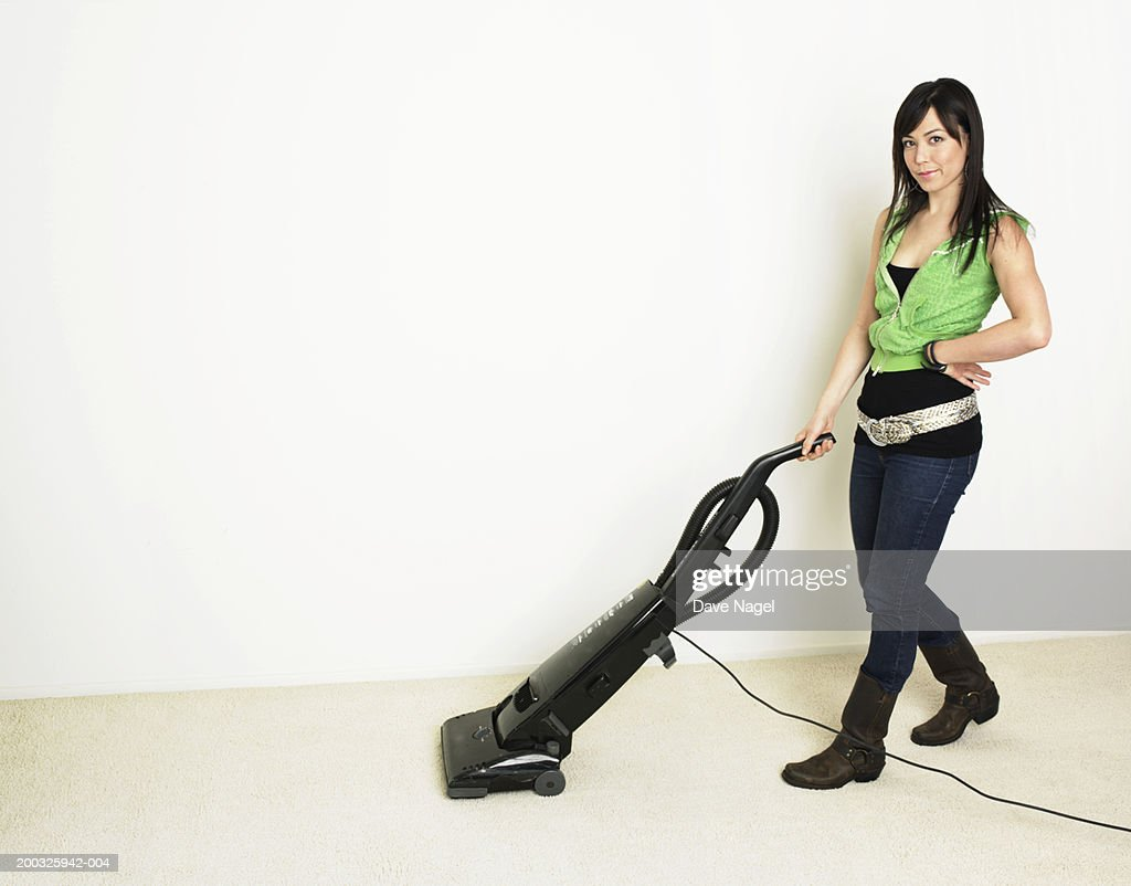 Young woman vacuming floor, portrait : Stock Photo