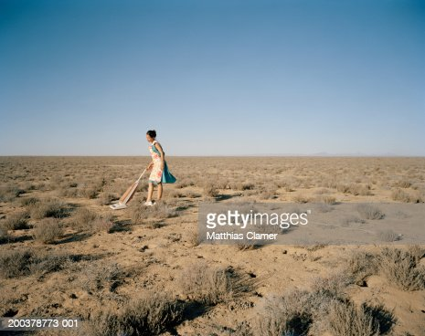 Young woman vacuming in desert, side view : Stock Photo