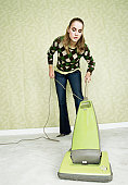 Young woman vacuuming carpet