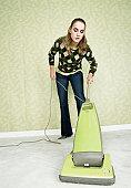 Young woman vacuuming carpet