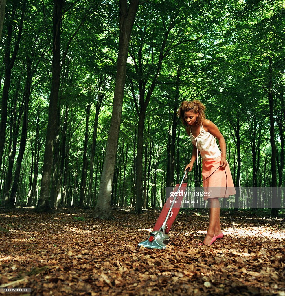Young woman vacuuming fallen leaves on forest floor : Stock Photo