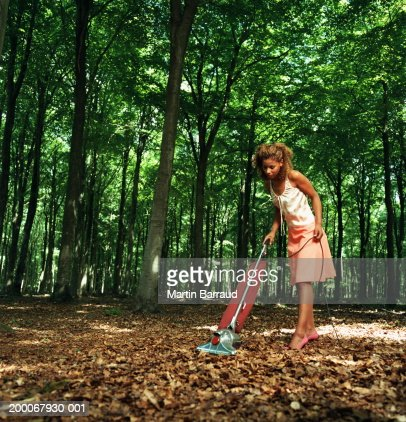 Young woman vacuuming fallen leaves on forest floor : ストックフォト