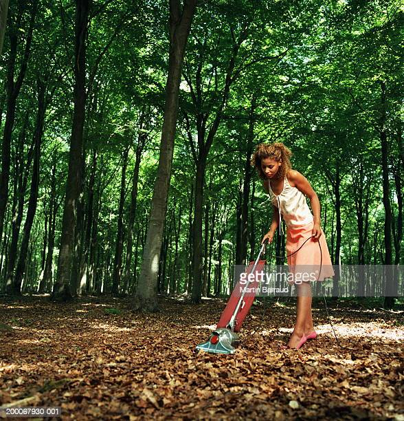 Young woman vacuuming fallen leaves on forest floor