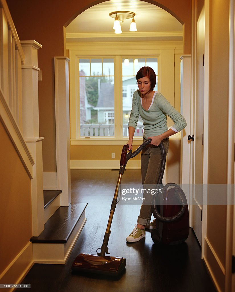 Young woman vacuuming floor in hallway of home : Stock Photo