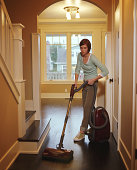 Young woman vacuuming floor in hallway of home