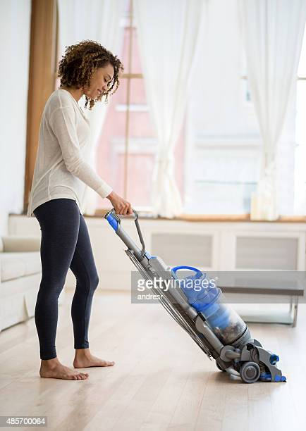 Young woman vacuuming her house