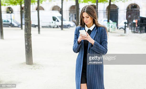 Young Woman Viewing Online Posts While Walking Outdoors