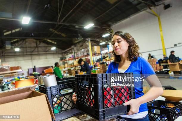 Jovem mulher volunteering para organizar os donativos em grande Banco alimentar