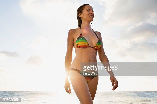 Young woman wading in water on tropical beach : Stockfoto