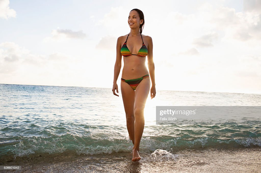Young woman wading in water on tropical beach : Foto de stock