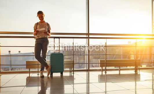 young woman waiting for flying at airport at window with suitcase : Stock Photo
