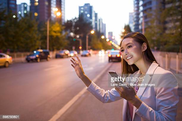 Young woman waiting for taxi with smart phone