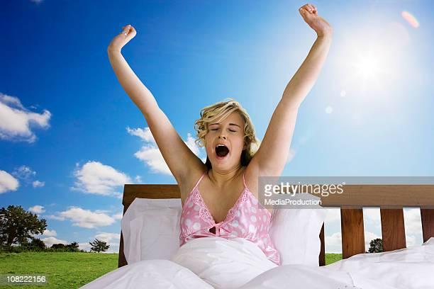 Joven mujer Despertando en la cama al aire libre