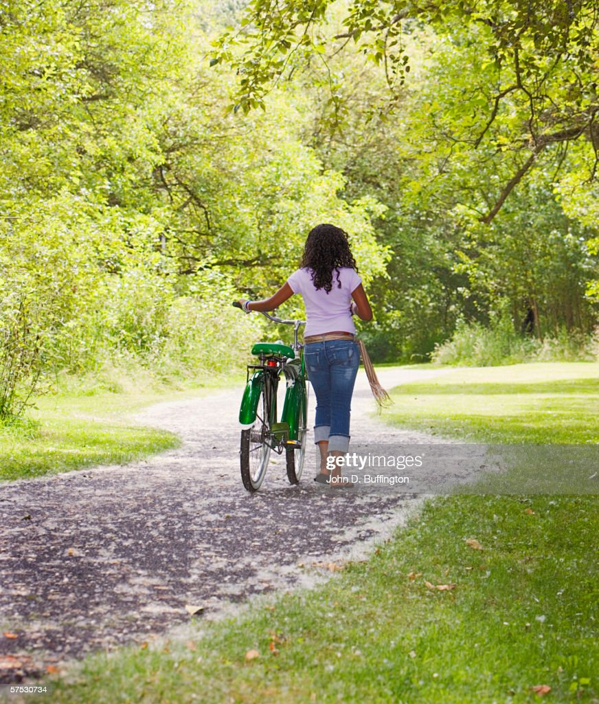 Young Woman Walking A Bike Down A Path Stock Photo Getty Images