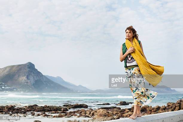 Young woman walking along cement block on beach, Cape Town, Western Cape, South Africa
